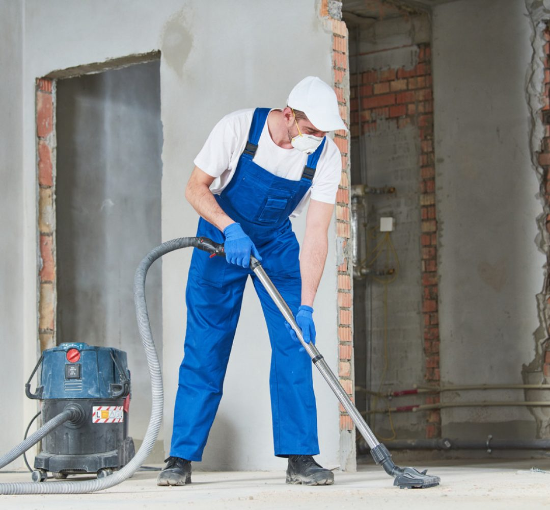 service man cleaning and removing construction dust with vacuum cleaner after repair